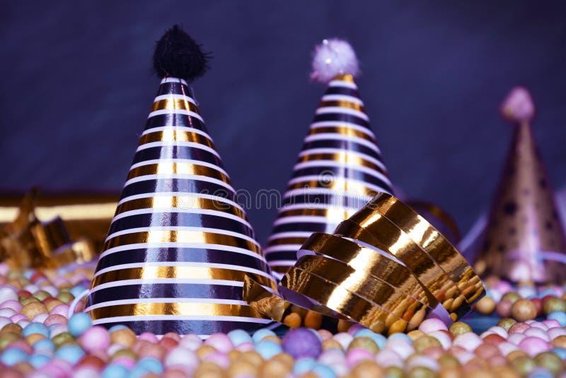 新年silvester或生日宴会帽子、金黄诗歌选飘带和五颜六色的泡沫球在黑暗的背景 免版税库存照片