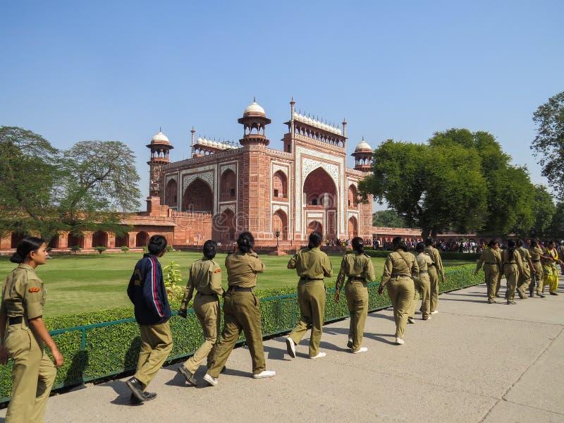 新德里,印度,2013年11月21日 制服的女孩去入口德里红堡 免版税库存照片