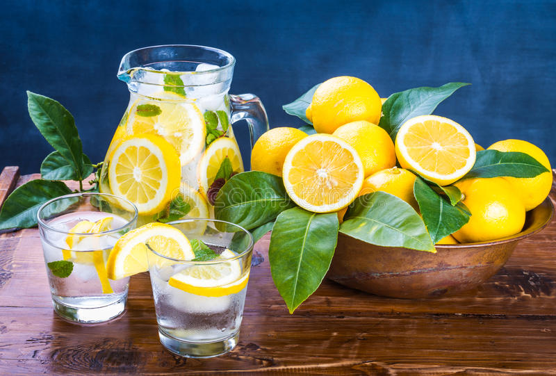 新戒毒所饮料、玻璃用柠檬水和薄菏在土气木背景 免版税库存照片