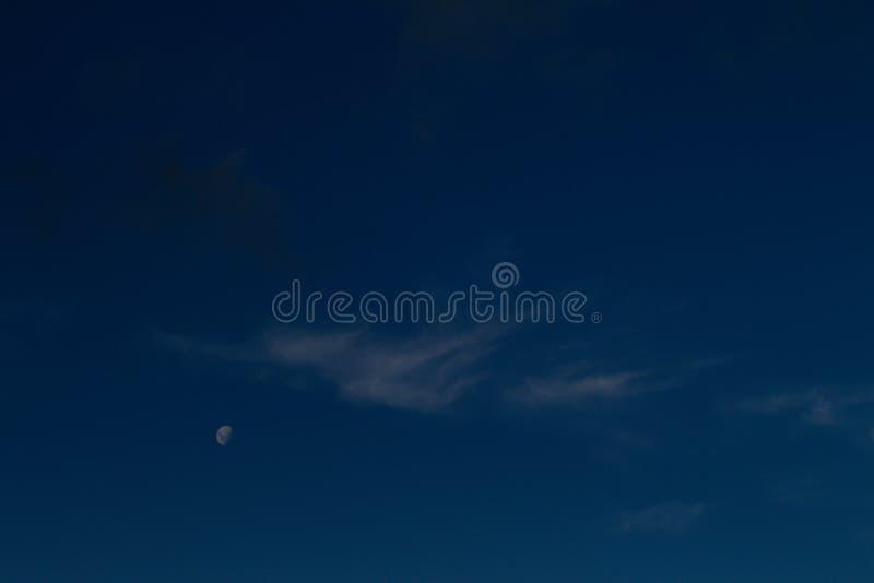 新月形月亮,在一朵小白色云彩旁边 免版税库存照片