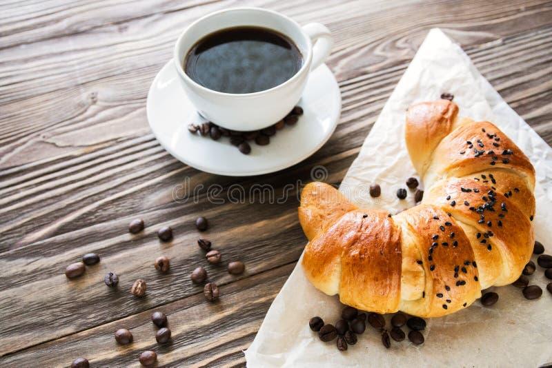 新月形面包、一个在土气一顿织地不很细木背景顶视图,舒适和可口的早餐的杯子速溶咖啡和咖啡豆 免版税库存照片