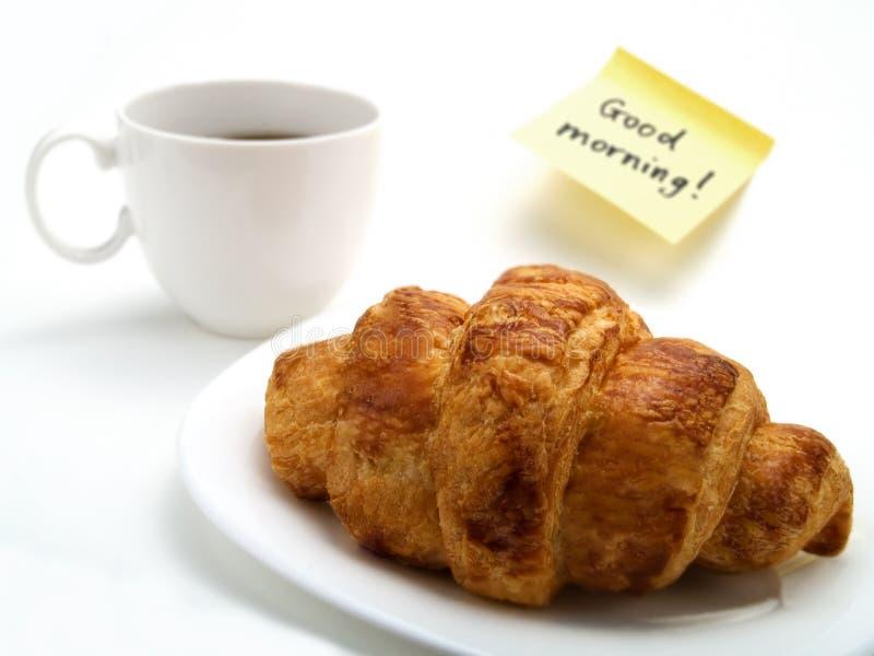 新月形面包、一杯咖啡和黄色附注 图库摄影