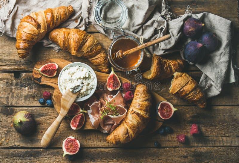 新月形面包、乳清干酪乳酪、无花果、新鲜的莓果、熏火腿和蜂蜜 库存照片