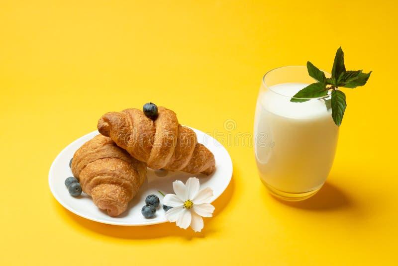 新月形面包、咖啡、花和berriies在黄色背景 免版税库存图片