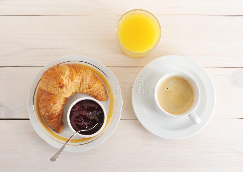 新月形面包、果酱、咖啡和橙汁在木背景 图库摄影