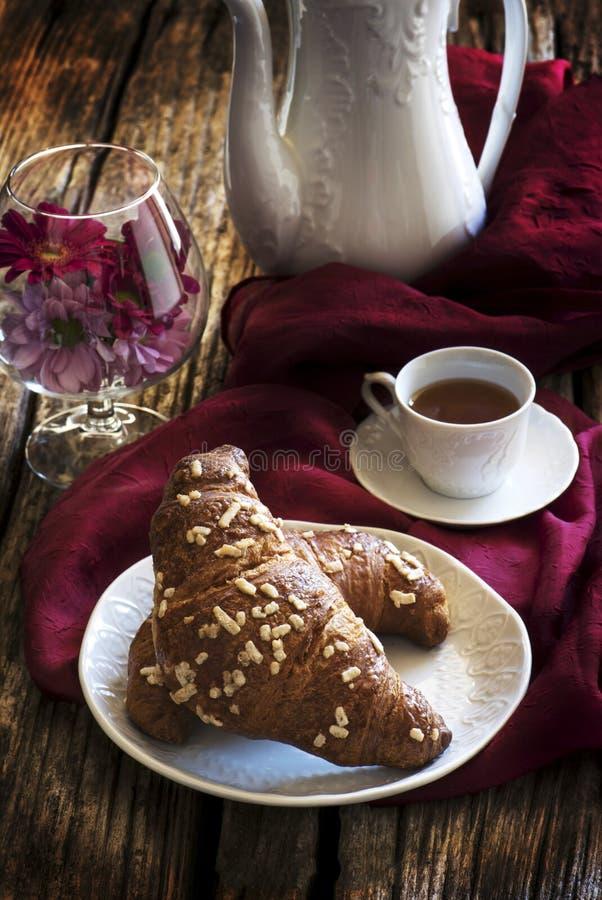新月形面包和咖啡与咖啡罐和板材 免版税库存照片