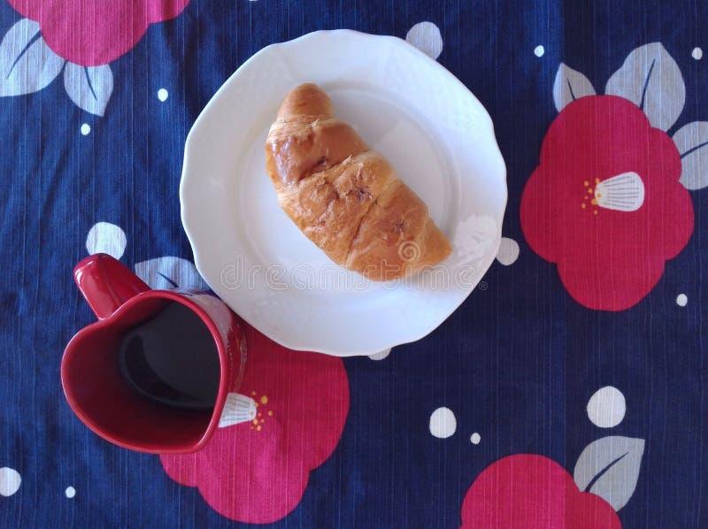 新月形面包和咖啡在桌上 免版税库存照片