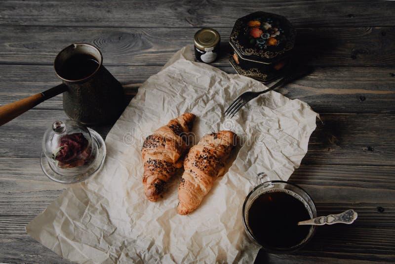 新月形面包用巧克力和咖啡在木桌上 免版税图库摄影