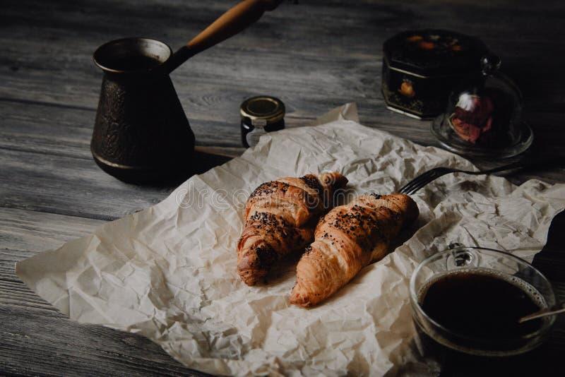 新月形面包用巧克力和咖啡在木桌上 免版税库存图片