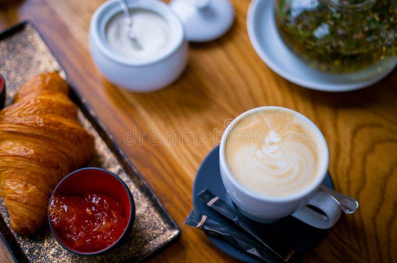 新月形面包用果酱和黄油 与泡沫的热奶咖啡咖啡在板材,顶视图的早餐法国新月形面包的 免版税库存图片