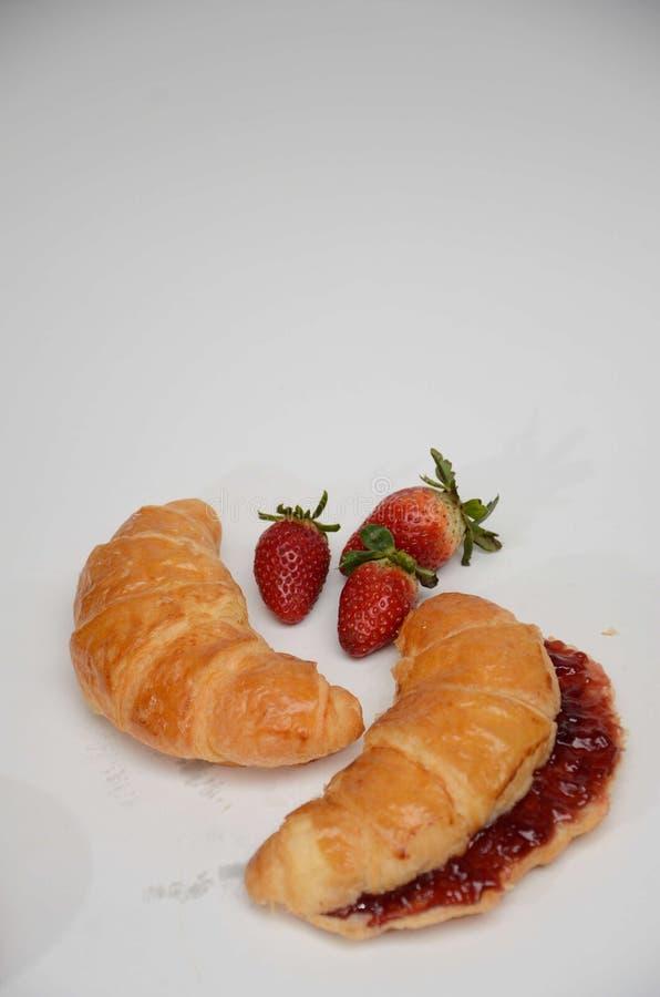 新月形面包用草莓和果酱 库存图片