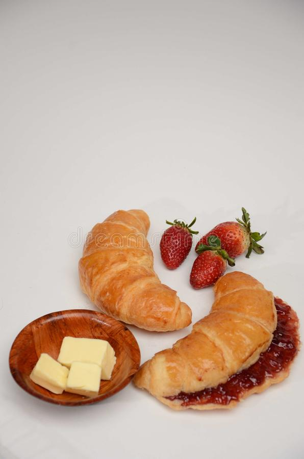 新月形面包用草莓酱和黄油 免版税库存图片