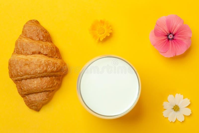 新月形面包,牛奶,在黄色背景的花 免版税库存照片