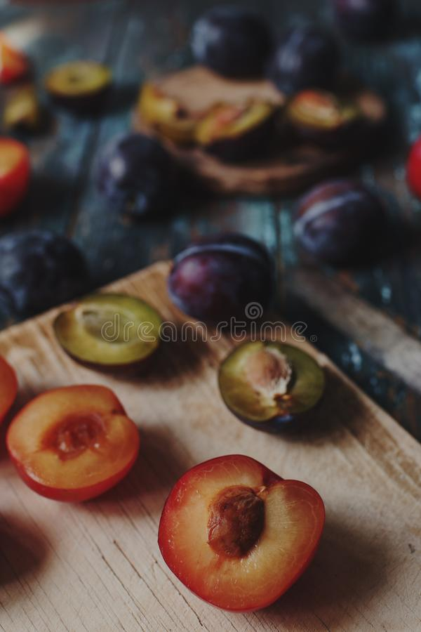 新有机李子和李子切片在木板和土气木桌,秋天收获,季节性果子,健康生活方式, s 免版税库存图片