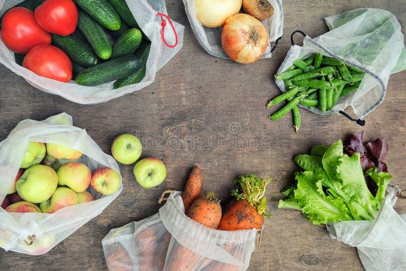 新有机蔬菜、水果和绿色在可再用的被回收的滤网产物袋子在木背景与拷贝空间 ? 免版税库存照片