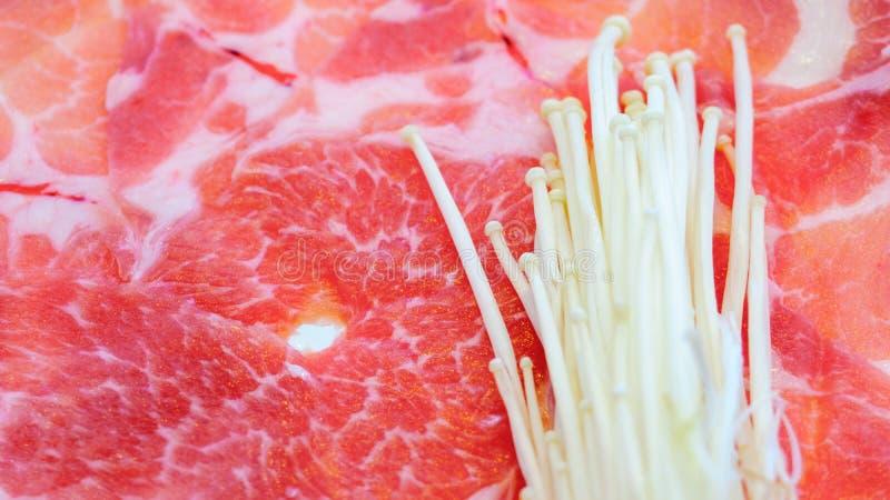 新未加工的使有大理石花纹的猪肉幻灯片和金黄针蘑菇或者在shubu的,在韩语的BBQ格栅板材堆积的enoki蘑菇的关闭 图库摄影