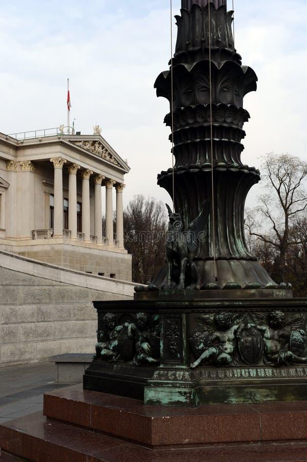 新来的人古铜色雕象 老街灯的装饰在奥地利议会大厦,维也纳,奥地利前面的 它被架设了  库存图片