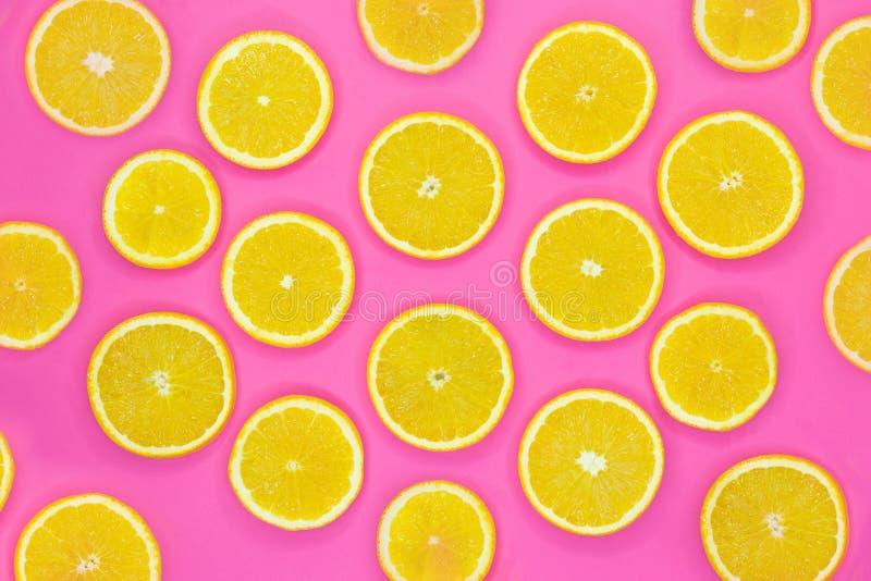 新橙色切片的五颜六色的果子样式在桃红色背景的 免版税库存照片