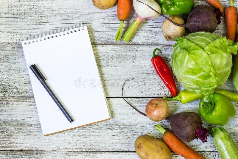 新水多的菜边界、空白的白色笔记薄与拷贝空间和笔在白色木背景,顶视图 免版税库存图片
