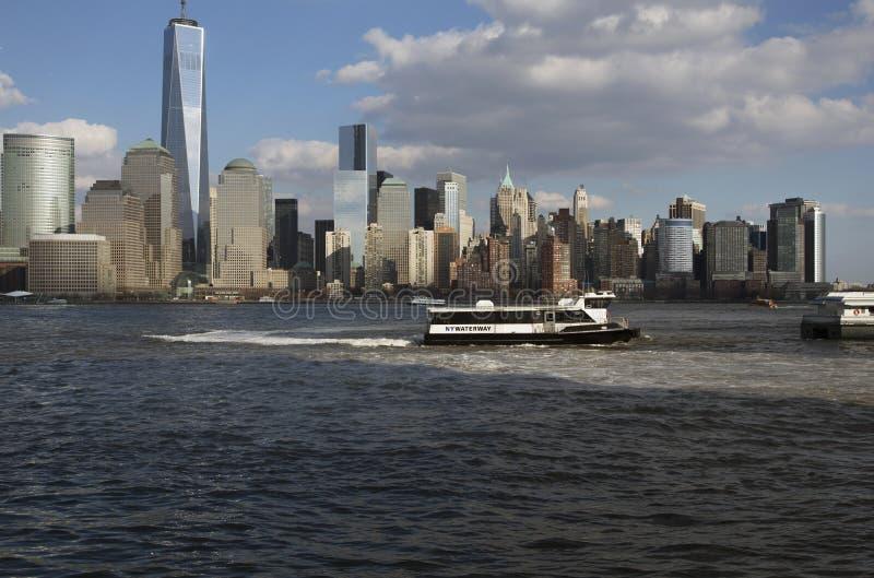 从新泽西,水出租汽车在以世界贸易中心一号大楼(1WTC),自由塔, Ne为特色的纽约地平线前面被看见 库存图片