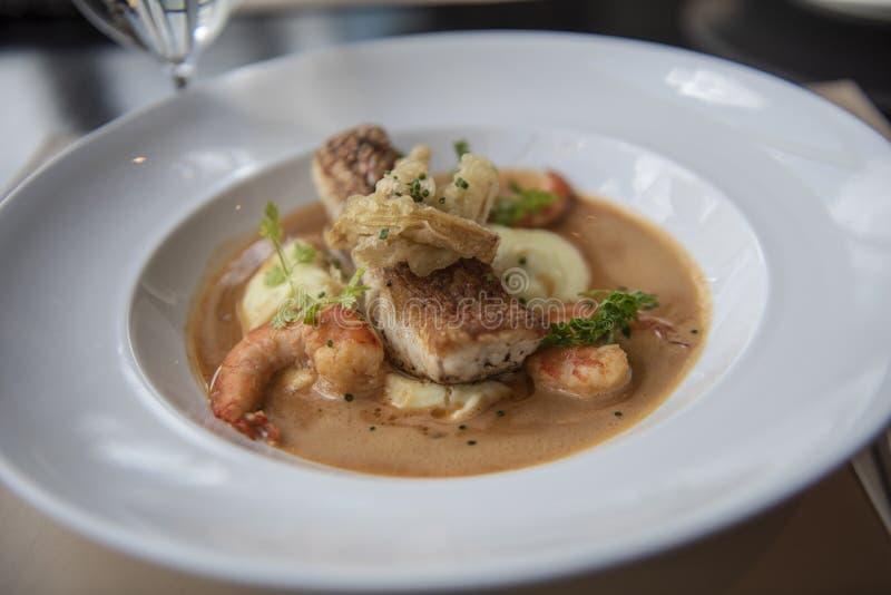 新海鲜菜单用红鲷鱼,虾,土豆和冠上用棕色小汤 库存图片