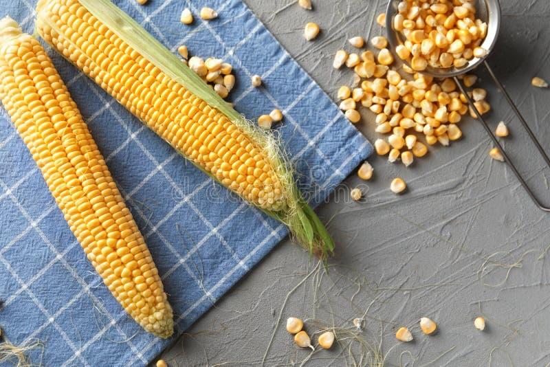 新玉米棒子和仁在桌上 库存照片