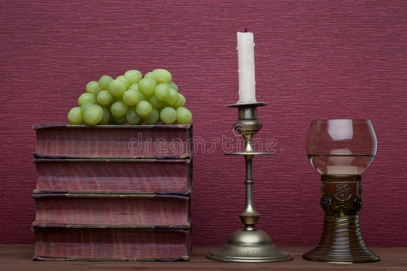 新生、rummer酒杯、旧书、葡萄和蜡烛台 免版税库存照片