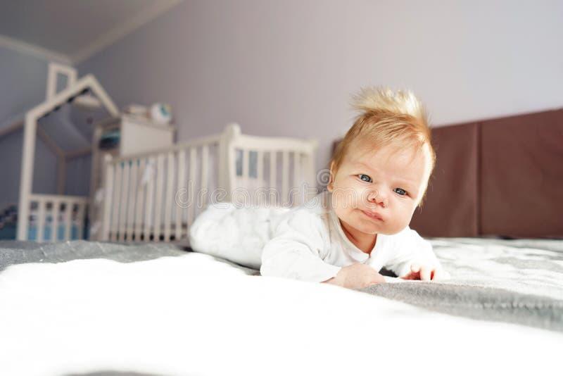 新生儿在他的胃说谎在床上的托儿所 免版税库存图片
