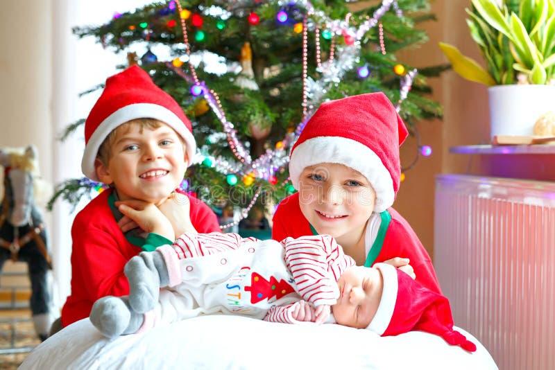 新生儿女孩和两哥哥在圣诞树附近哄骗圣诞老人帽子的男孩 免版税库存照片