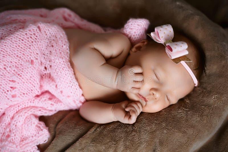 新生儿女孩睡觉逗人喜爱,用软的桃红色围巾盖,整洁地被折叠在与一个小头的一支笔下有一把桃红色弓的,集合 图库摄影