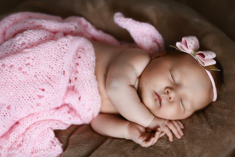 新生儿女孩睡觉逗人喜爱,用软的桃红色围巾盖,整洁地被折叠在与一个小头的一支笔下有一把桃红色弓的,集合 免版税图库摄影