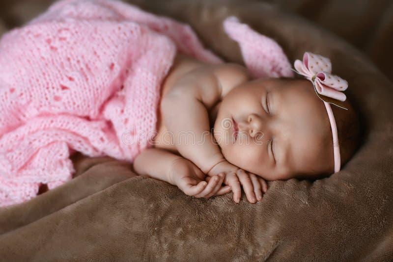 新生儿女孩睡觉逗人喜爱,用软的桃红色围巾盖,整洁地被折叠在与一个小头的一支笔下有一把桃红色弓的,集合 库存图片
