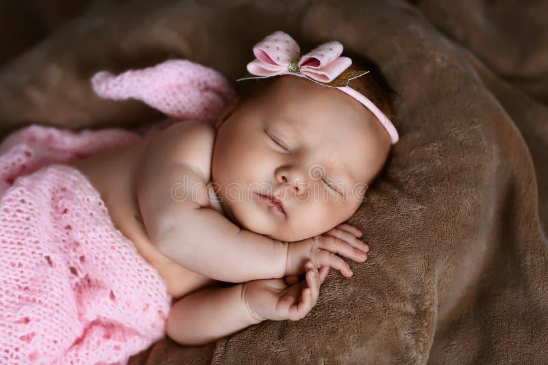 新生儿女孩睡觉逗人喜爱,用软的桃红色围巾盖,整洁地被折叠在与一个小头的一支笔下有一把桃红色弓的,集合 库存照片