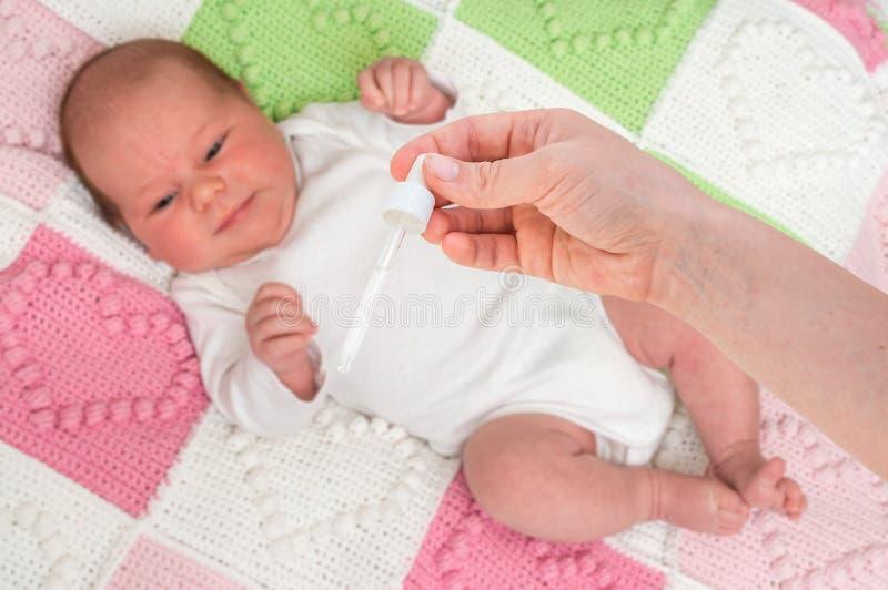 新生儿得到滴鼻剂用食盐水 免版税图库摄影