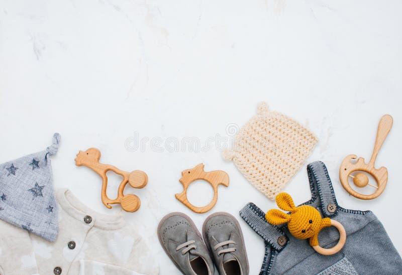 新生儿衣物、鞋子和玩具在轻的大理石背景 免版税库存图片