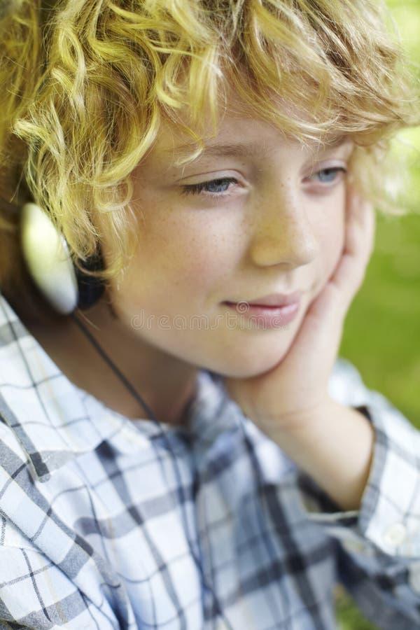 新男孩佩带的耳机户外 图库摄影