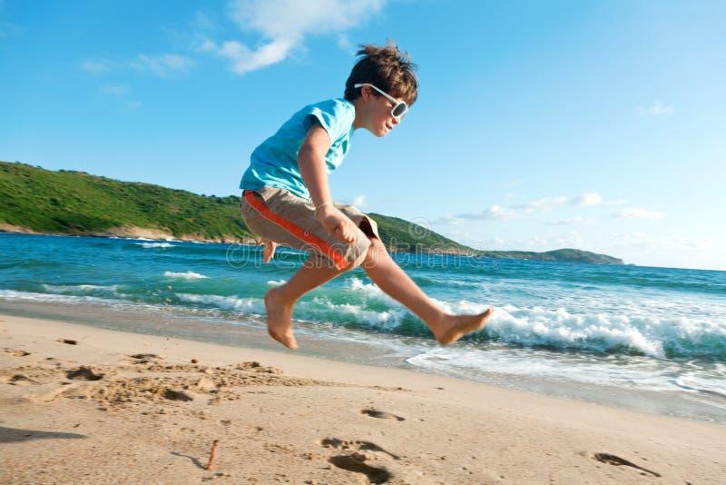 新男孩在海运跳 免版税库存照片