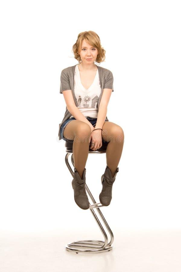 新白肤金发的女孩坐高凳 免版税图库摄影