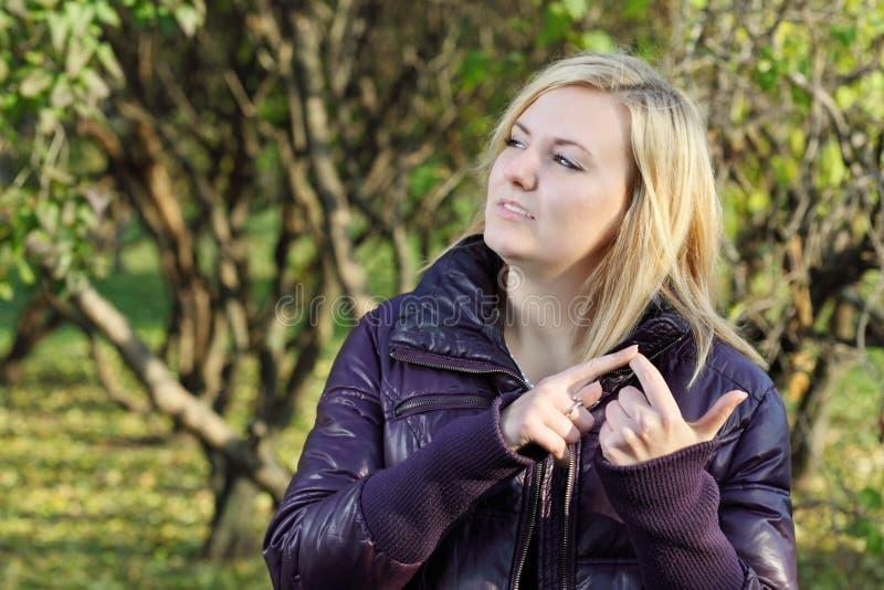 新白肤金发的妇女在他的手指作梦并且计数在公园 库存图片