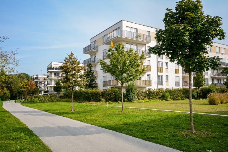 新的公寓-现代住宅发展在绿色都市解决 免版税库存照片