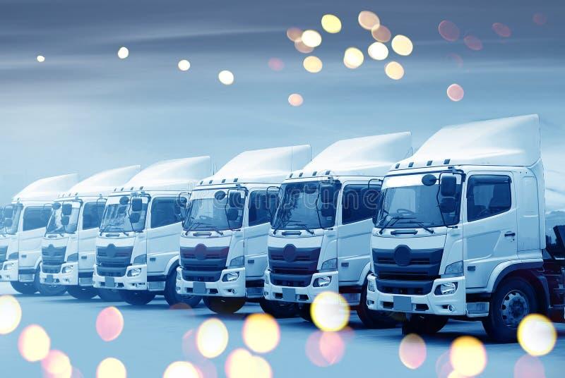 新的卡车队在蓝色口气的围场停放transporation的 库存照片