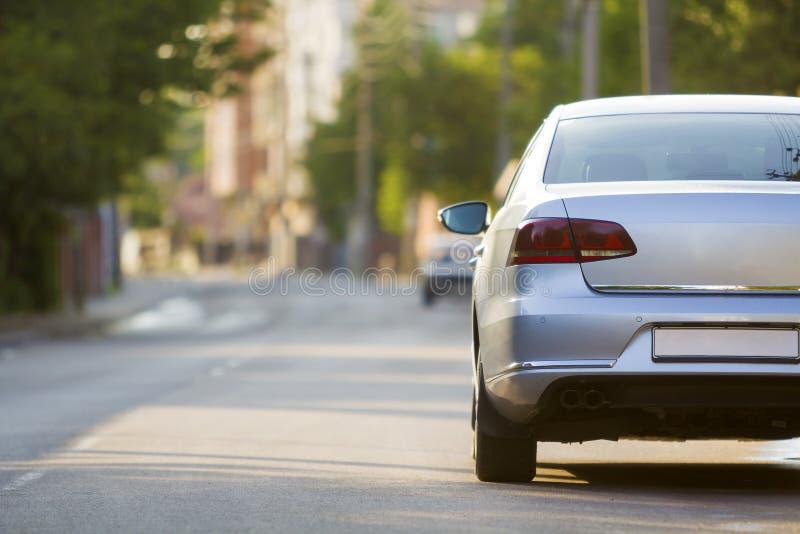 新的发光的昂贵的银色汽车移动的alon特写镜头后面视图  图库摄影