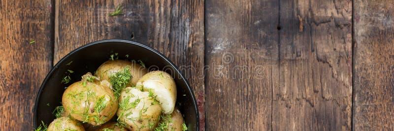 新的土豆 煮的土豆用莳萝和黄油在一个黑碗在一张木桌上 土气样式 顶视图, 库存图片