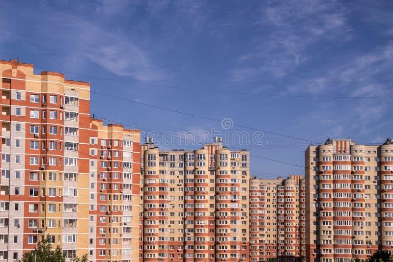 新的多层的居民住房有天空蔚蓝背景 公寓购买概念 图库摄影