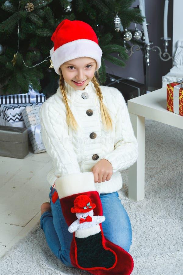 新的女孩考虑圣诞节的礼物或 图库摄影