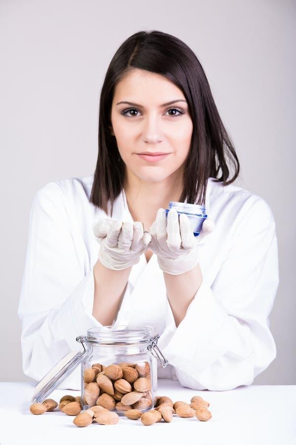 介绍新的奶油的年轻透视皮肤病学家医生 有机治病的治疗医学化妆用品 库存图片