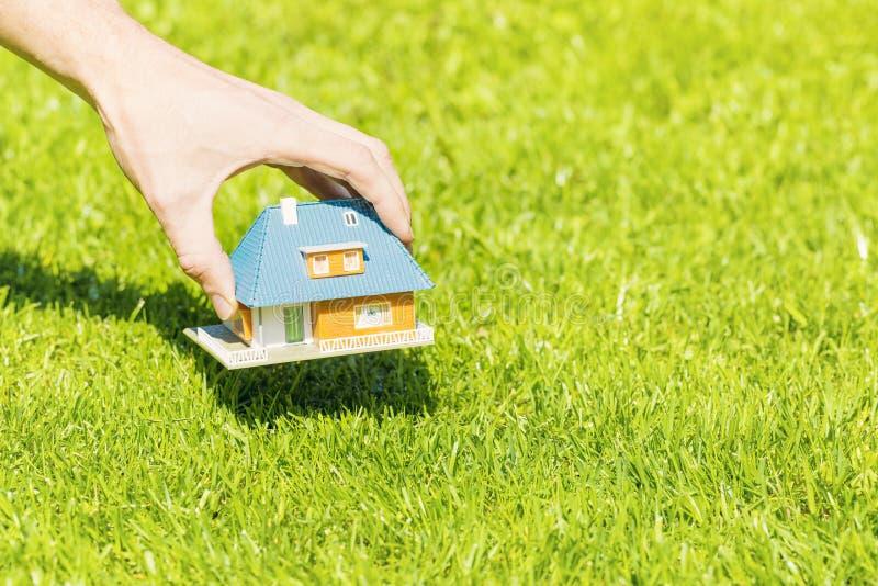 新的家庭概念,把房子比例模型放的手在草上 免版税库存照片