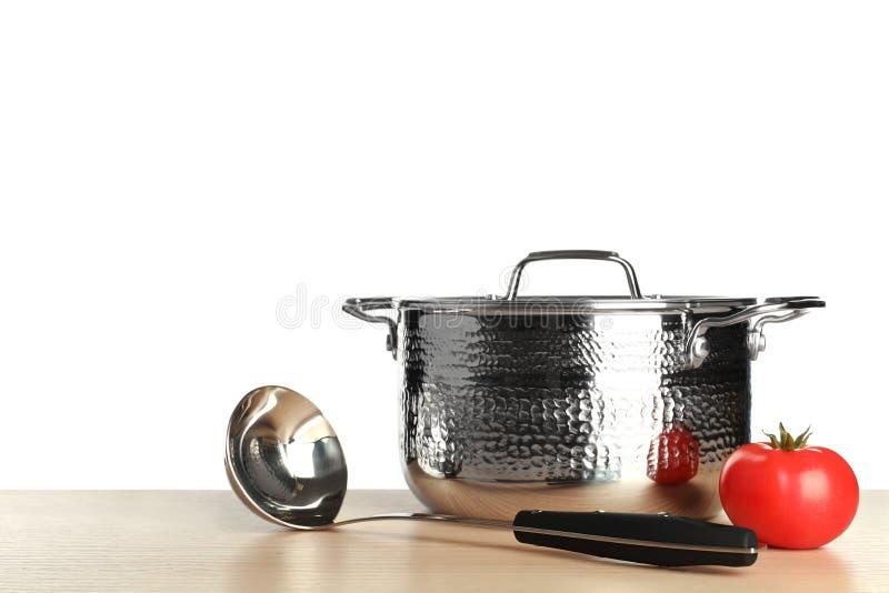 新的干净的平底深锅、杓子和蕃茄在桌上反对白色背景 免版税库存照片