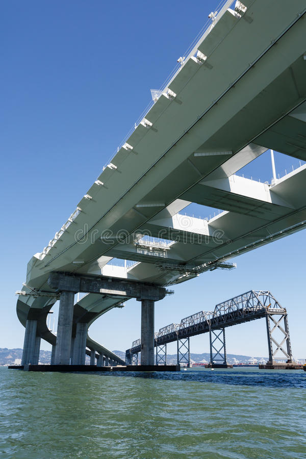 新的旧金山湾桥梁的超结构的下面的看法有老桥梁的在背景中 免版税库存照片