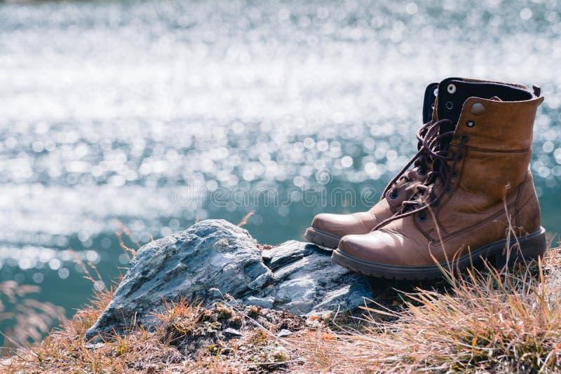 新的棕色皮鞋的关闭在山湖观点 冒险概念,徒步旅行者,旅行 复制空间 免版税库存照片